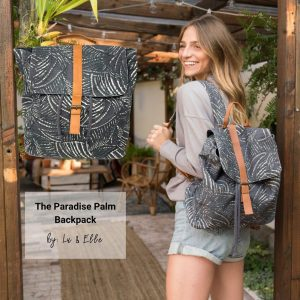 Woman standing in walkway with backpack smiling