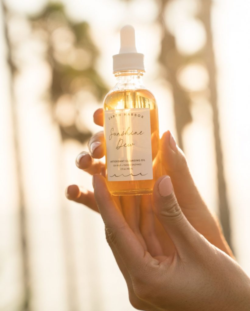 Hand holding a glass bottle of face oil